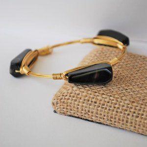 Three black stones on a gold bangle bracelet